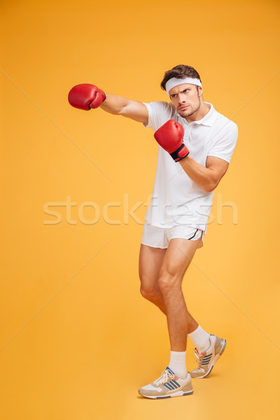 Strong young man boxer in red gloves standing and fighting Stock photo © deandrobot
