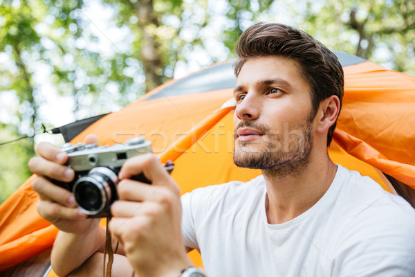 Man with old camera sitting near touristic tent in forest Stock photo © deandrobot