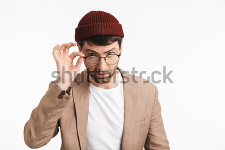 Handsome young man in blue shirt putting on the hat Stock photo © deandrobot
