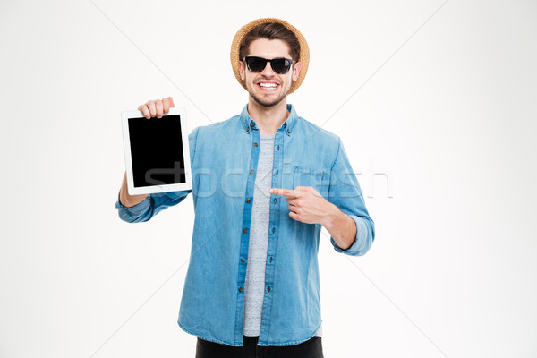 Cheerful young man holding and pointing on blank screen tablet Stock photo © deandrobot