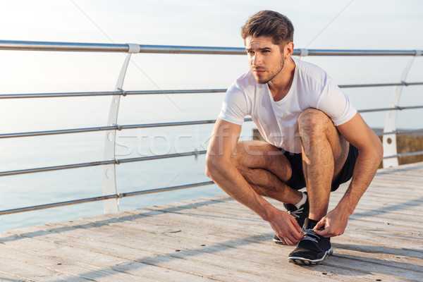 Man athlete laces his sneakers on pier Stock photo © deandrobot