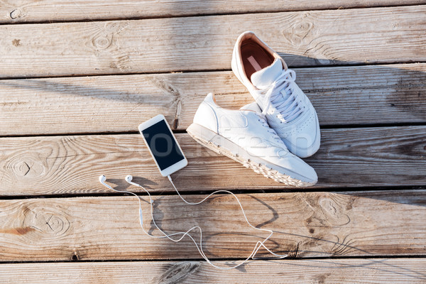 Sport concept - pair of white sneakers, smartphone and earphones Stock photo © deandrobot