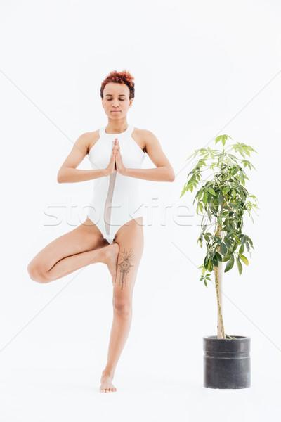 Beautiful african american young woman practicing vrishasana Stock photo © deandrobot