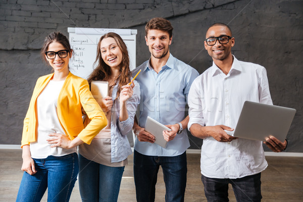 Group of cheerful business people with tablet and laptop Stock photo © deandrobot
