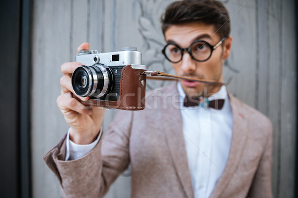 Happy stylish nerd with camera outdoors Stock photo © deandrobot