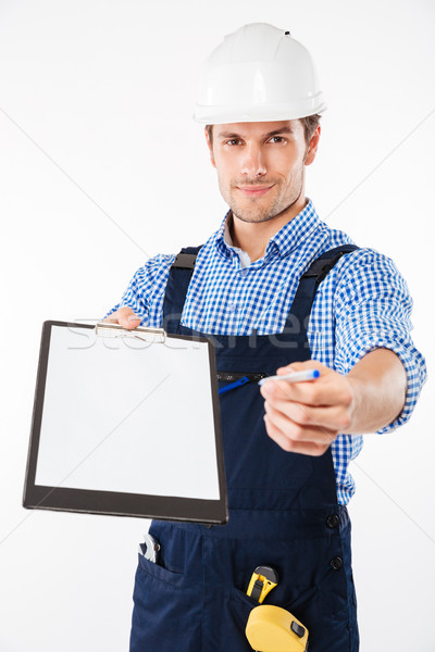 Smiling hadsome builder giving blank sheet of paper Stock photo © deandrobot