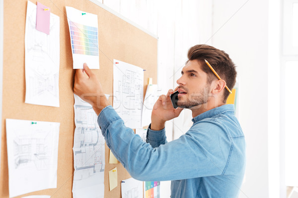 Businessman looking at task board and talking on the phone Stock photo © deandrobot