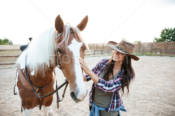 Smiling woman cowgirl enjoying taking care of horse in village Stock photo © deandrobot