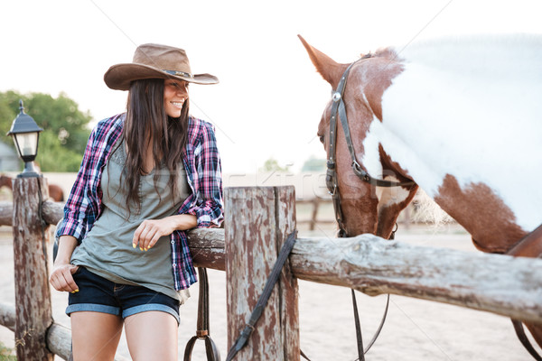 Smilng pretty young cowgirl standing with her horse on ranch Stock photo © deandrobot