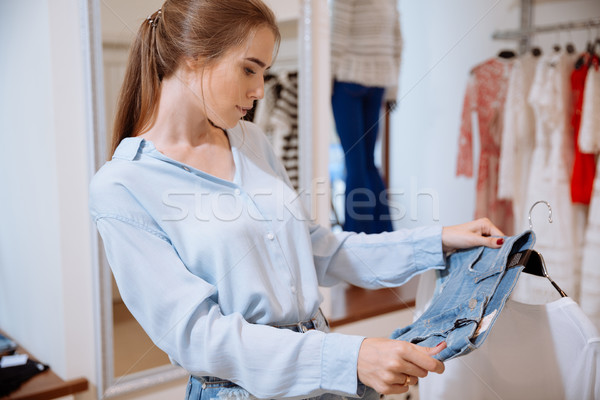 Cute young woman thinking and choosing clothes in clothing shop Stock photo © deandrobot