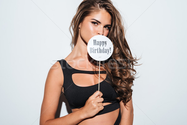 Image of girl in bikini covering mouth with sign Stock photo © deandrobot
