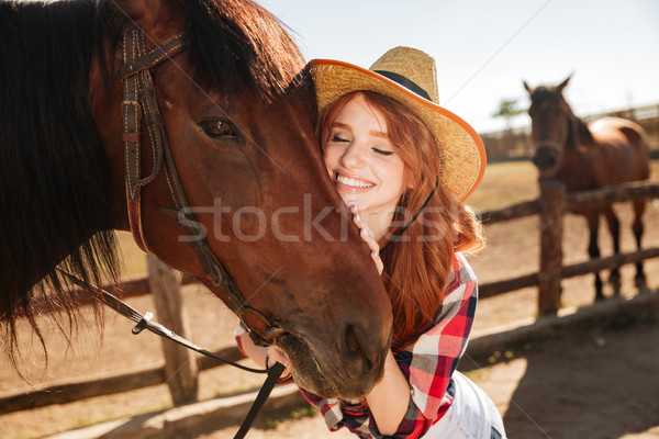 Happy tender young woman cowgirl hugging her horse Stock photo © deandrobot