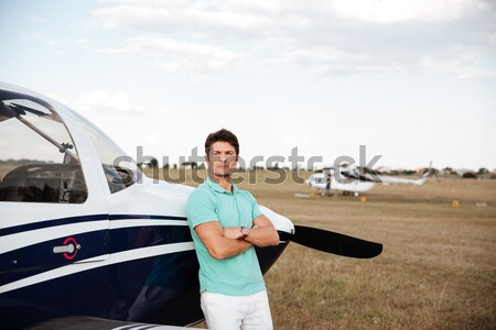 Smiling man standing near small airlane Stock photo © deandrobot