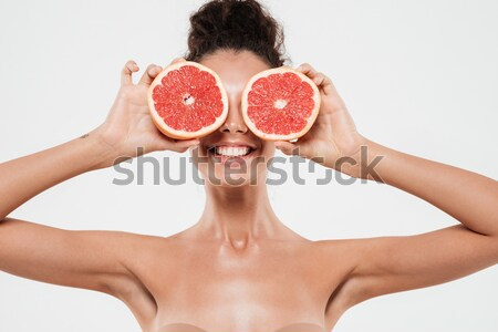 Smiling woman with grapefruit in front of her eye Stock photo © deandrobot