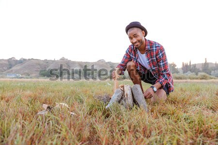 Smiling african man sitting and making campfire outdoors Stock photo © deandrobot