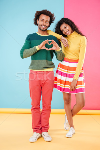 Happy couple in love standing and showing heart by hands Stock photo © deandrobot