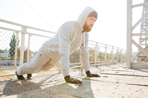 Handsome young fitness man doing push-up exercises outdoors Stock photo © deandrobot
