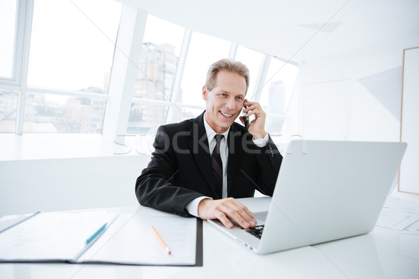 Elderly business man talking at phone by the table Stock photo © deandrobot
