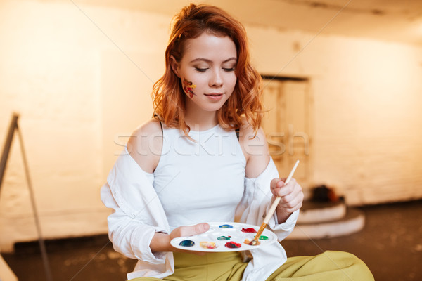 Beautiful young redhead lady painter with oil paints on face Stock photo © deandrobot