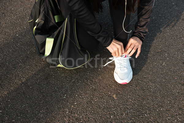 Cropped photo of woman runner tying laces Stock photo © deandrobot