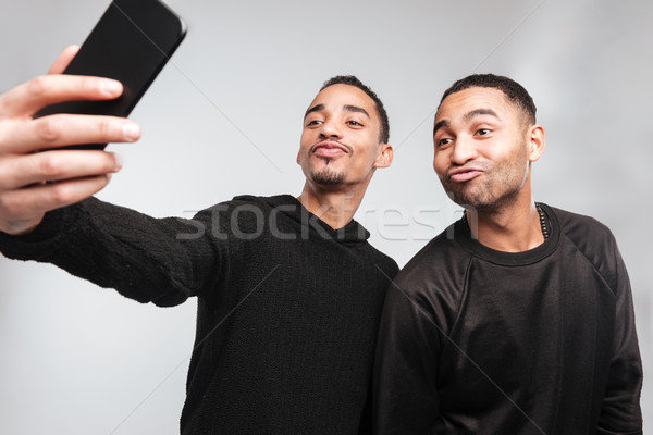 Young funny african men make a selfie. Stock photo © deandrobot