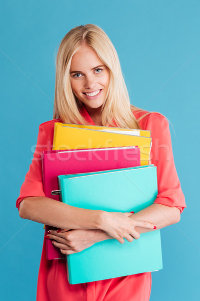 Smiling pretty young woman holding colorful folders with documents Stock photo © deandrobot
