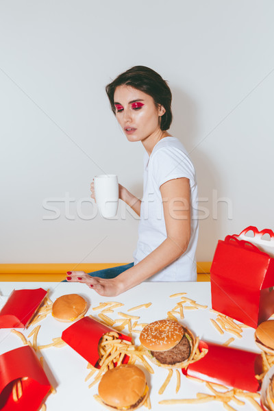 Woman with white mug sitting and refusing from fast food Stock photo © deandrobot