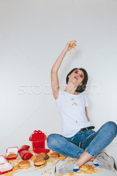 Joli jeune femme manger frites françaises blanche Photo stock © deandrobot