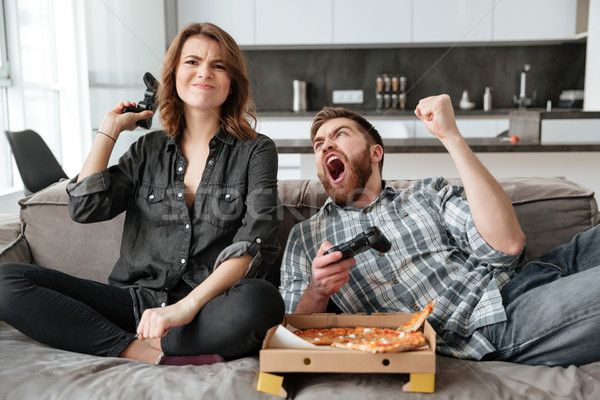 Attractive couple playing games with console and eating pizza. Stock photo © deandrobot
