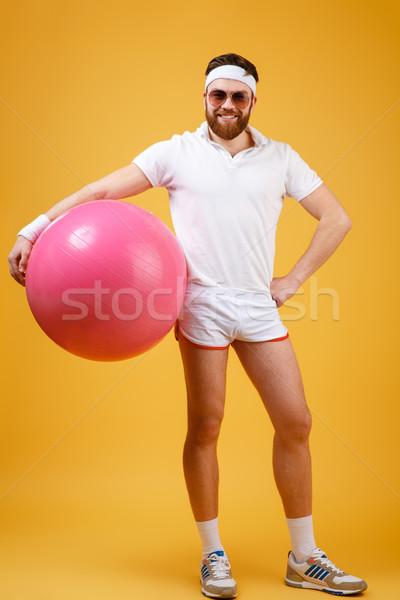 Vertical image of sportsman holding fitness ball Stock photo © deandrobot