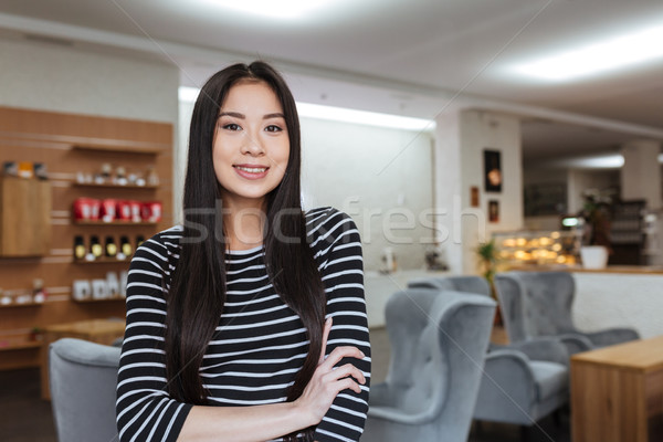 Happy Asian woman with crossed arms in cafeteria Stock photo © deandrobot