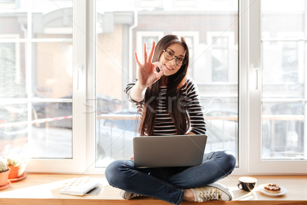 Asian woman on windowsill with laptop showing ok sign Stock photo © deandrobot