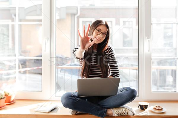 Asya kadın pencere eşiği dizüstü bilgisayar neden Stok fotoğraf © deandrobot
