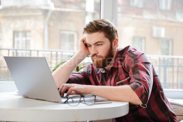 Konsantre sakallı genç dizüstü bilgisayar kullanıyorsanız bilgisayar görüntü Stok fotoğraf © deandrobot