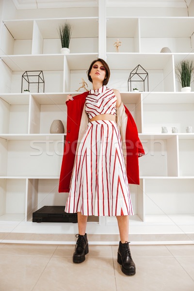 Beautiful young woman standing and taking off her red coat Stock photo © deandrobot