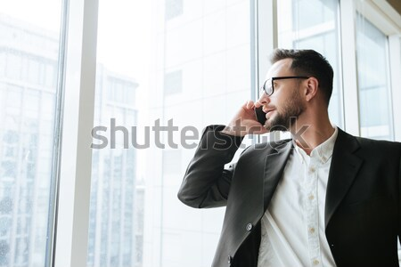 Happy Bearded business man talking on phone and looking away Stock photo © deandrobot