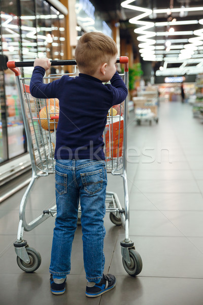 Vertical image of young boy with shopping trolley Stock photo © deandrobot