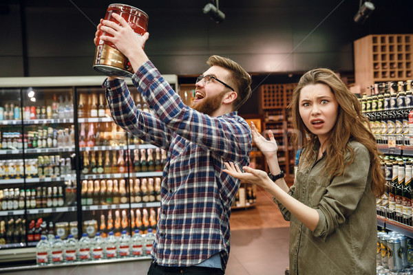 Displeased woman showing at man with keg of beer Stock photo © deandrobot