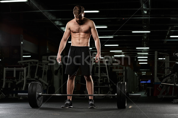 Handsome sports man make sport exercises with barbell Stock photo © deandrobot