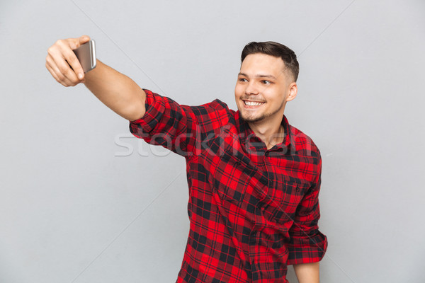 Handsome young man in plaid shirt making selfie Stock photo © deandrobot