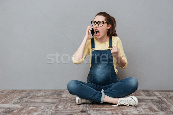 Pregnant angry screaming woman talking by mobile phone. Stock photo © deandrobot