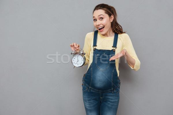 Pregnant happy woman holding clock Stock photo © deandrobot