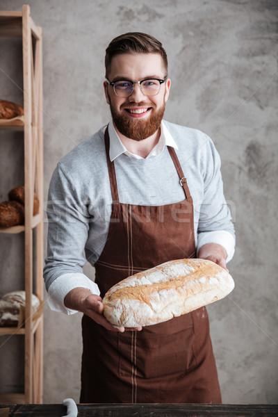 Derűs fiatalember pék áll pékség tart Stock fotó © deandrobot