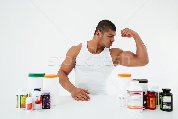 Sportoló mutat bicepsz kép fiatal komoly Stock fotó © deandrobot