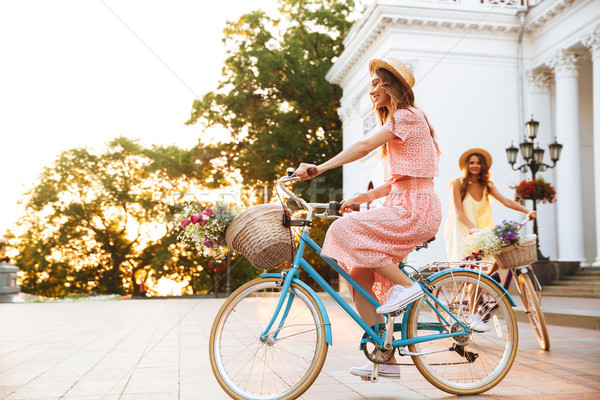 Two pretty smiling girls on a bicycle ride together Stock photo © deandrobot