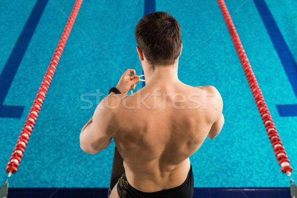 Rear view of a man preparing swimming goggles Stock photo © deandrobot