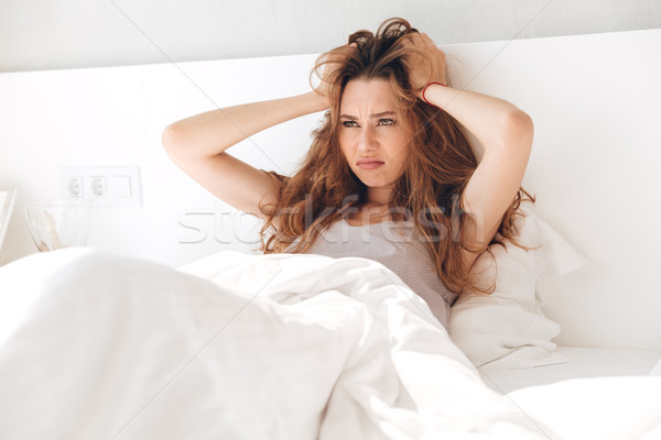 Annoyed woman holding her head in bed Stock photo © deandrobot