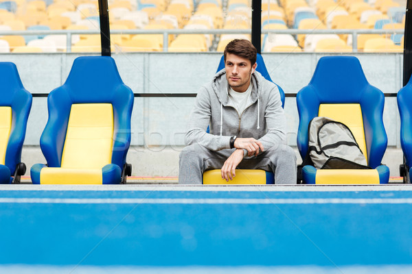 Young male athlete in sportswear sitting on a stadium seats Stock photo © deandrobot