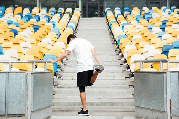 Fiatal sportoló nyújtás láb izmok edzés Stock fotó © deandrobot