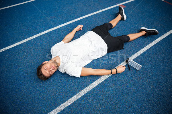 Tired sportsman lying on a racetrack with bottle of water Stock photo © deandrobot